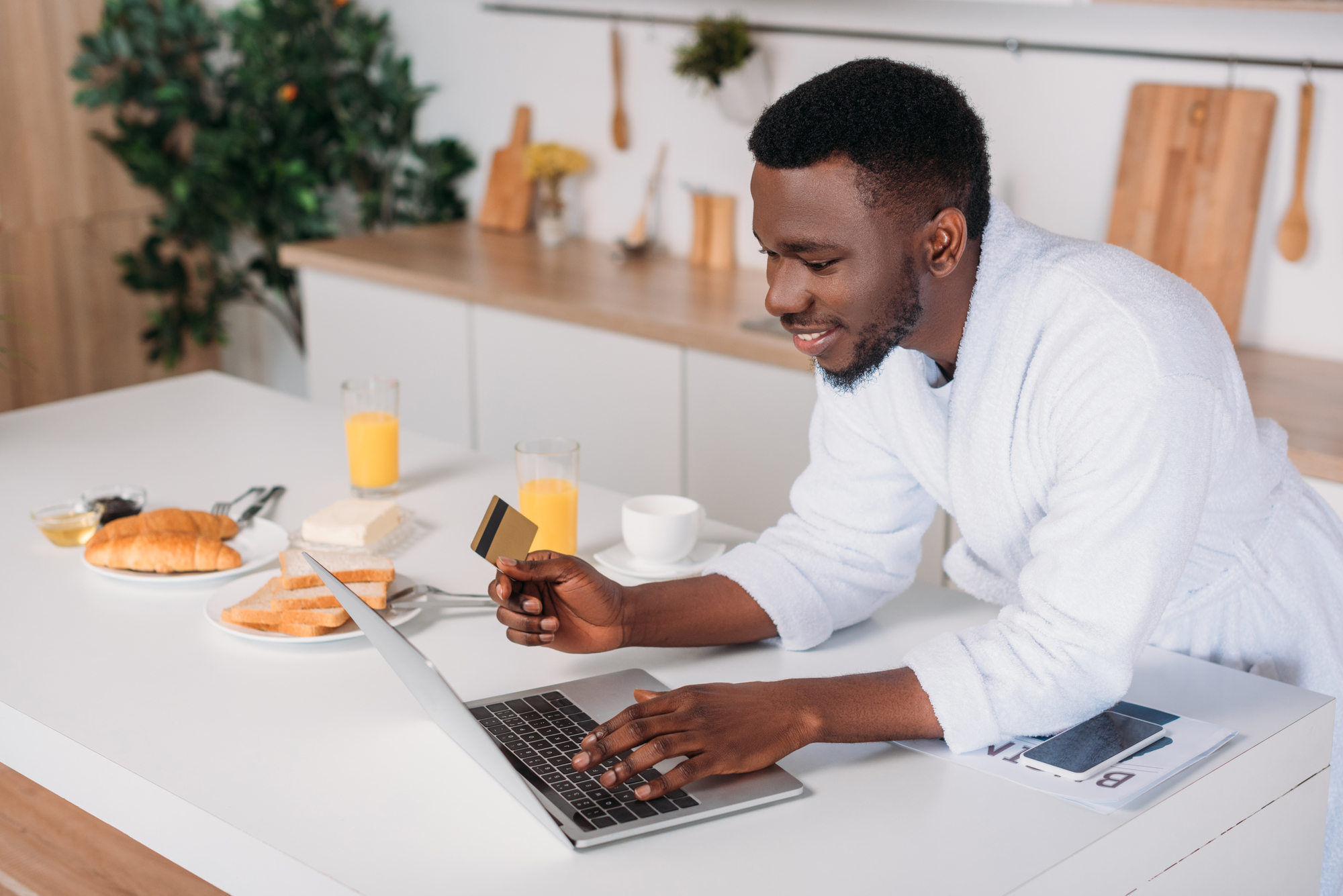 African american man doing online shopping and standing with credit card in kitchen