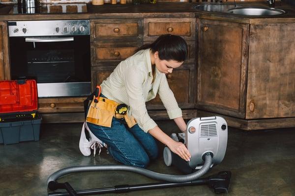 Attractive young repairwoman fixing vacuum cleaner on floor of kitchen