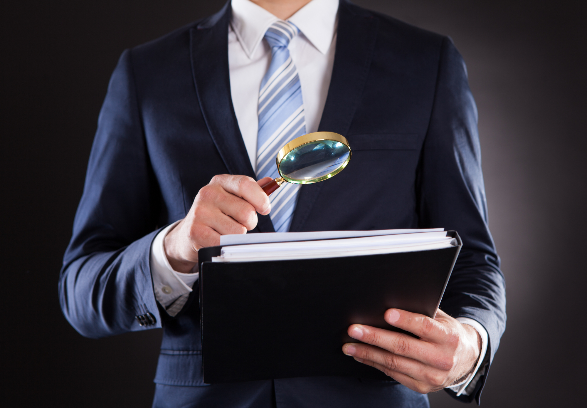 Businessman Examining Documents With Magnifying Glass