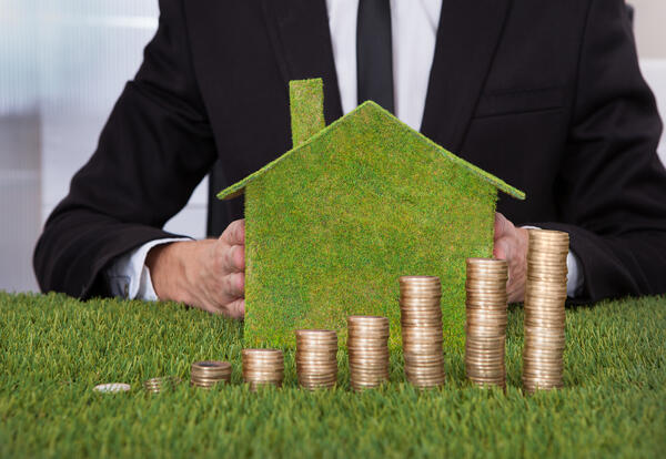 Businessman With Stack Of Coins And Eco Friendly House