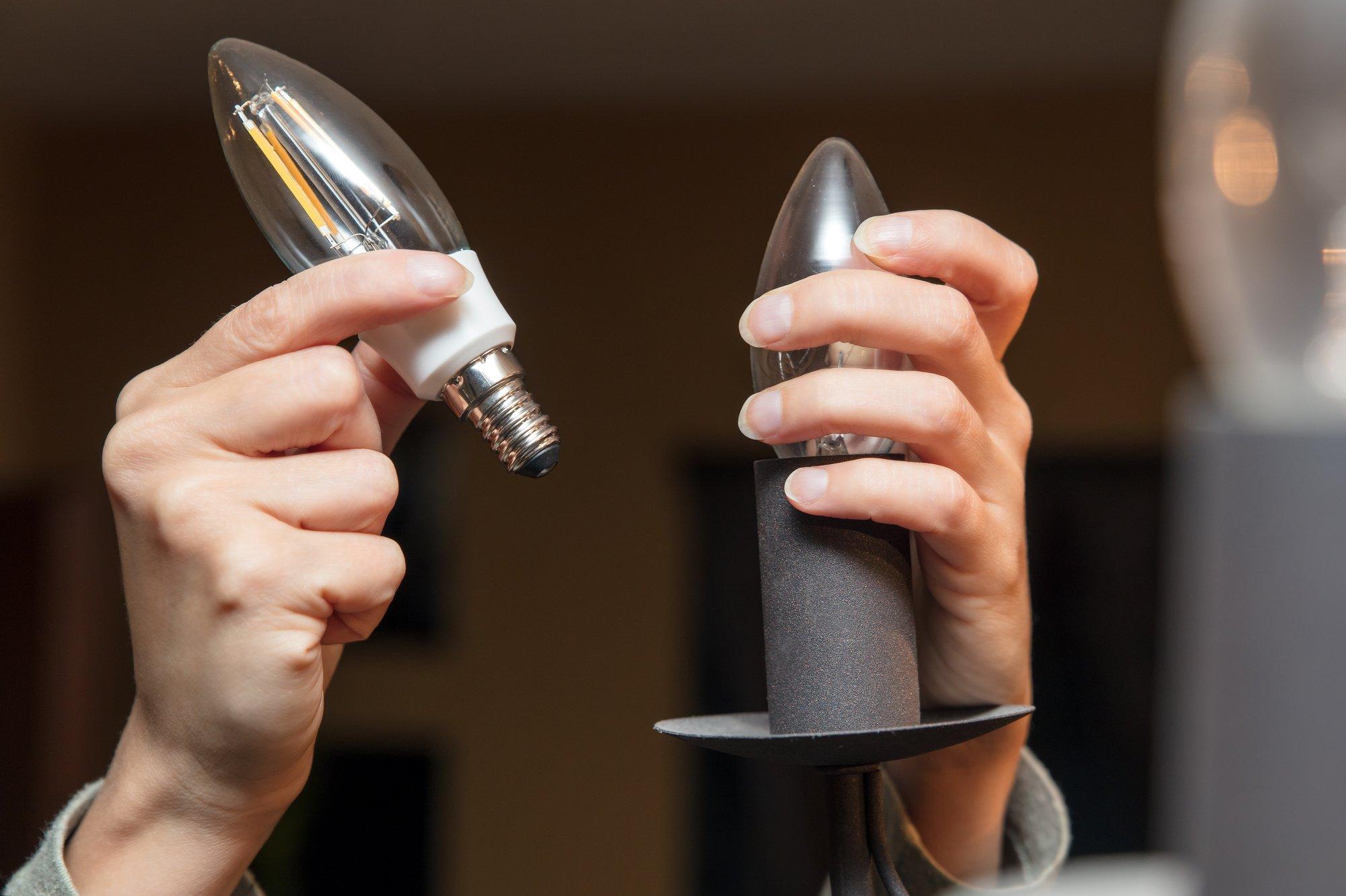 Closeup, woman changing a light bulb, energy saving lamp, electrictiy