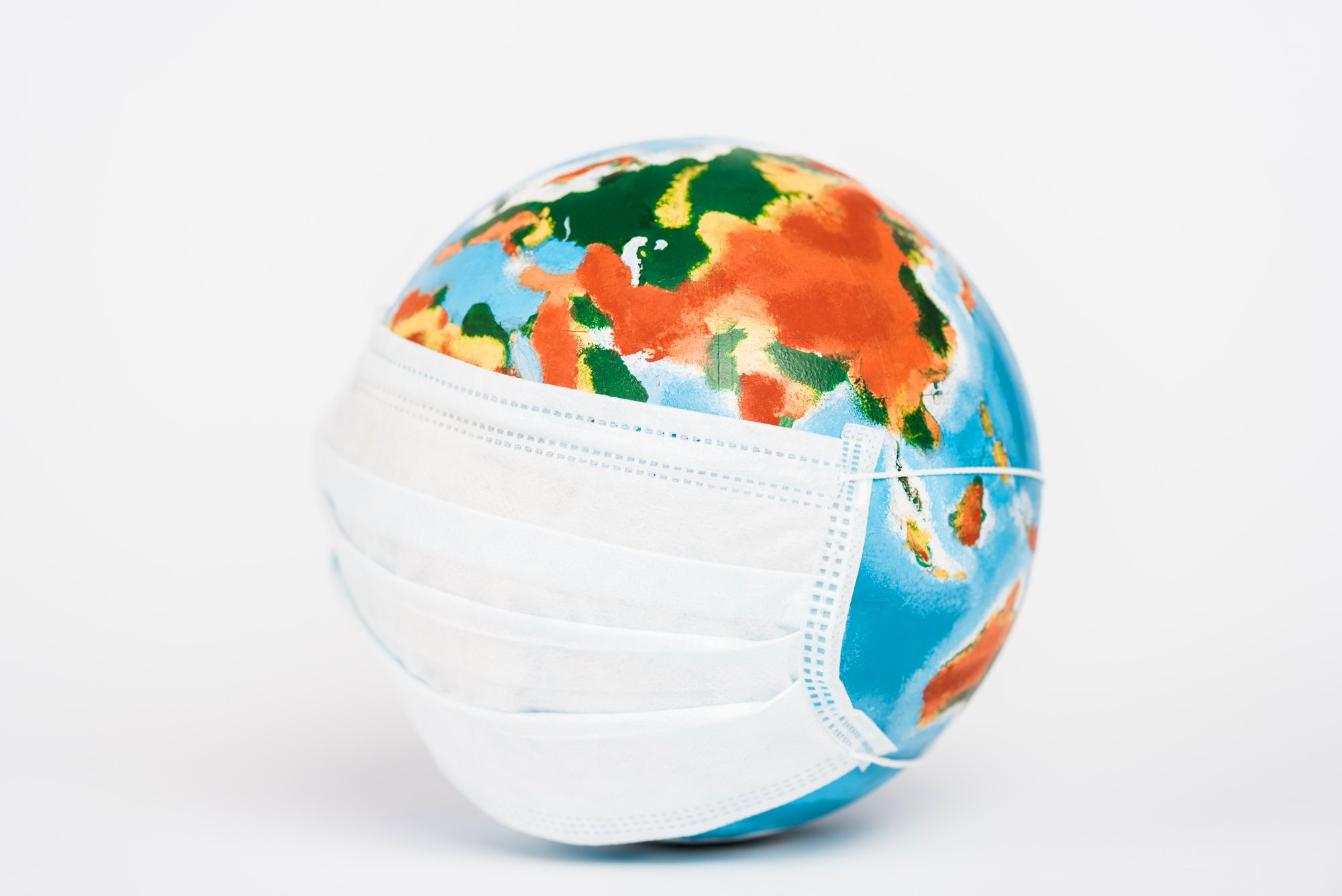 Colorful globe in medical mask on white