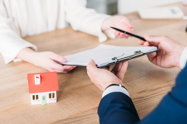 Cropped shot of realtor giving pen and clipboard with loan agreement to customer near house model