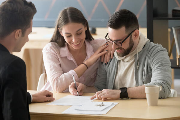 Excited couple sign purchase contract in realtor office