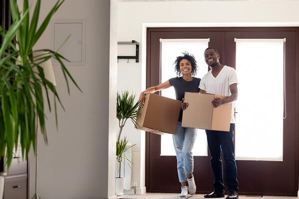 Happy african couple holding big boxes entering modern house