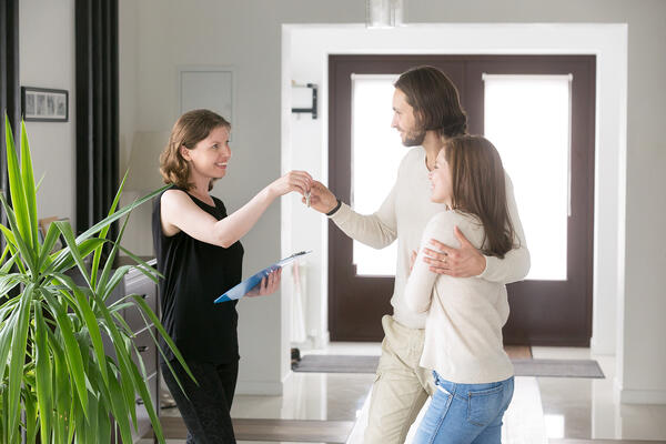 Happy couple receiving house keys from realtor