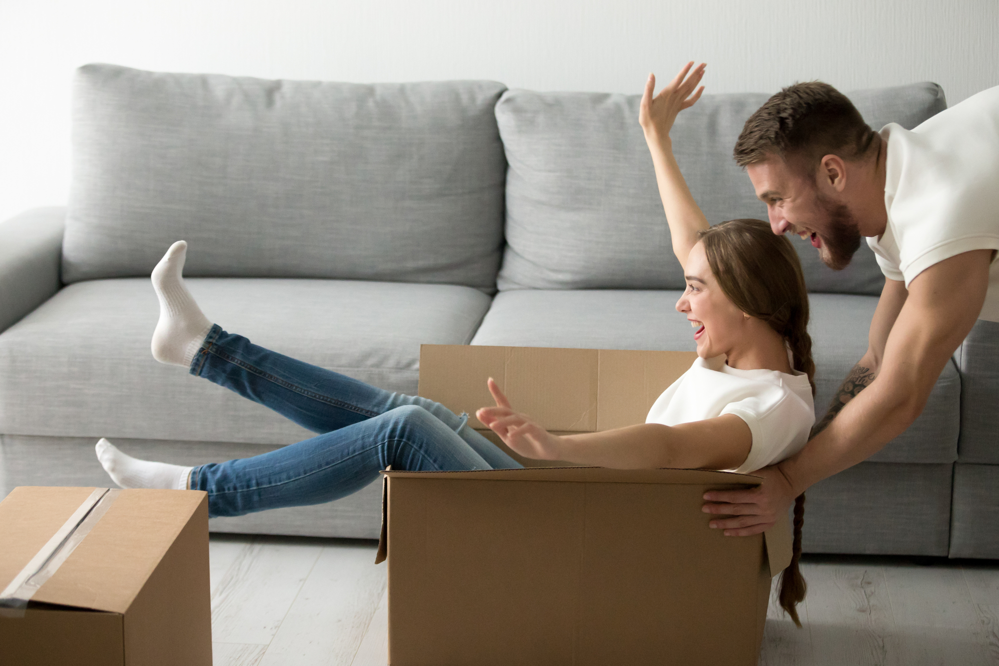 Happy couple riding in boxes having fun unpacking boxes