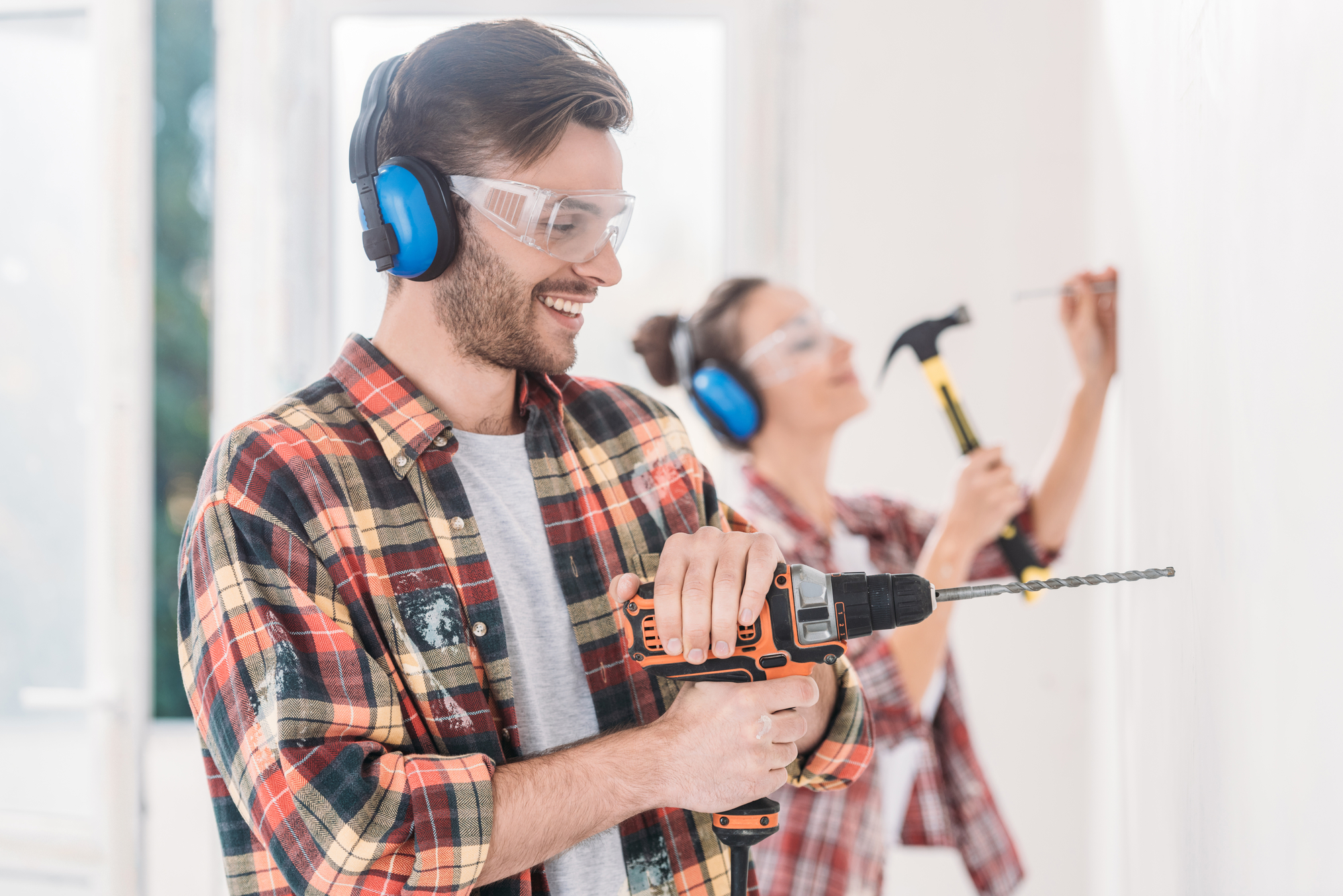 Happy young man using electric drill during house repairment