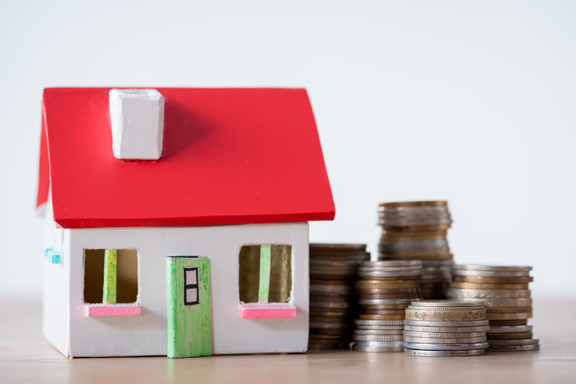 House model with red roof and white walls and stacks of metal coins isolated on grey
