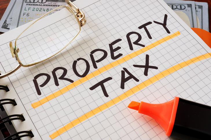 Notebook with property tax sign on a table. Business concept