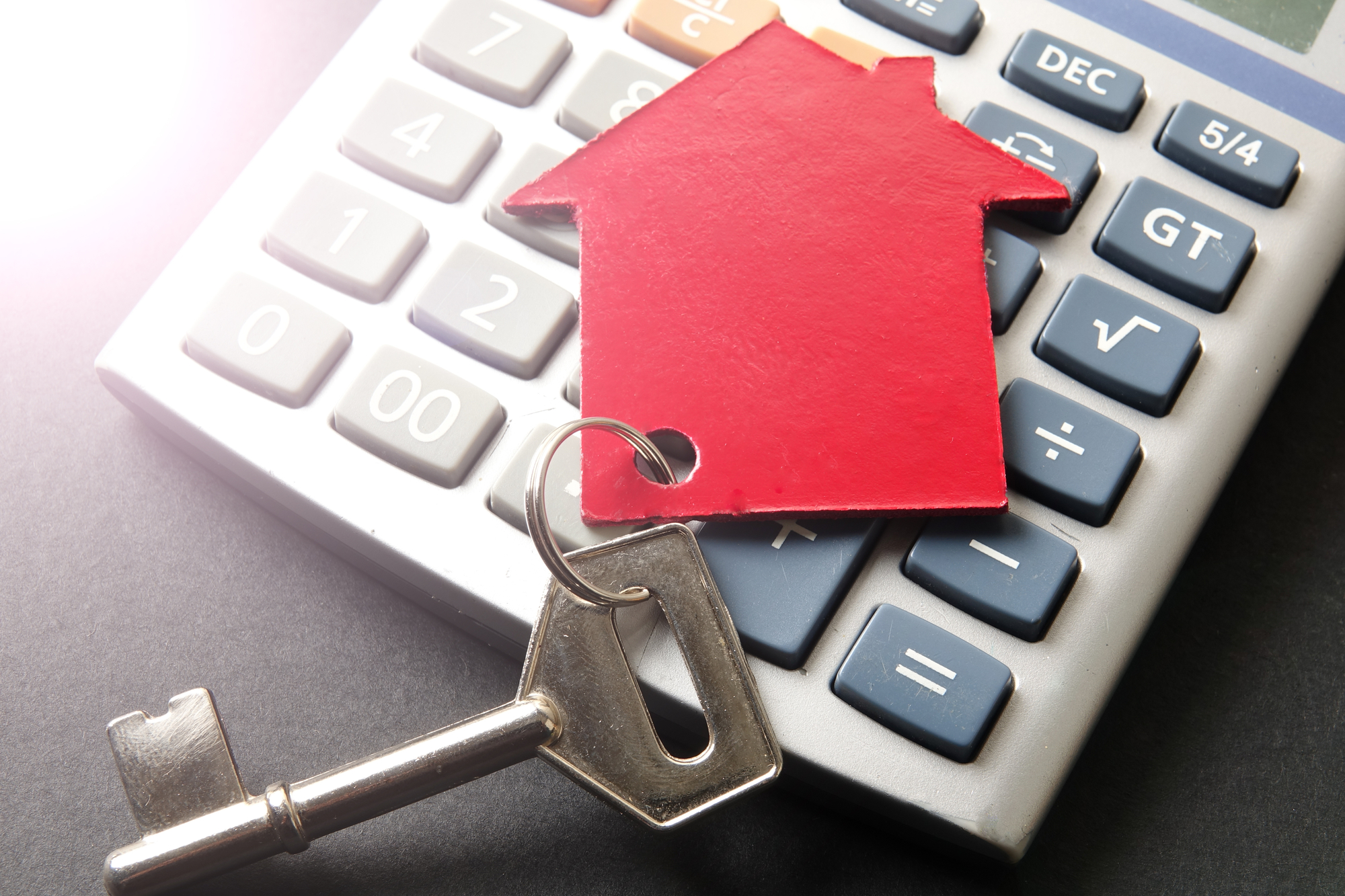 Red small house and steel key on calculator over black backgroun