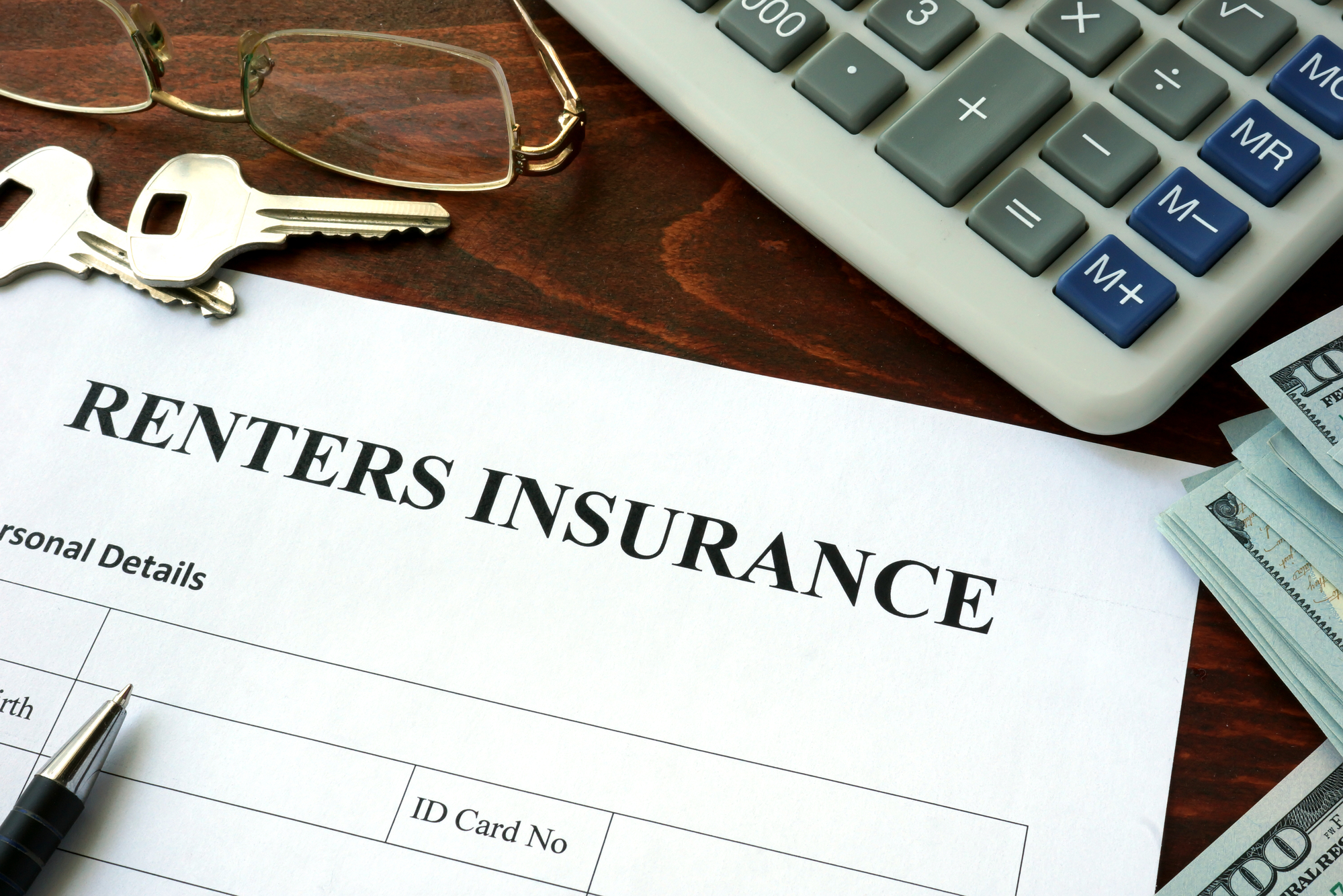 Renters insurance form and dollars on the table