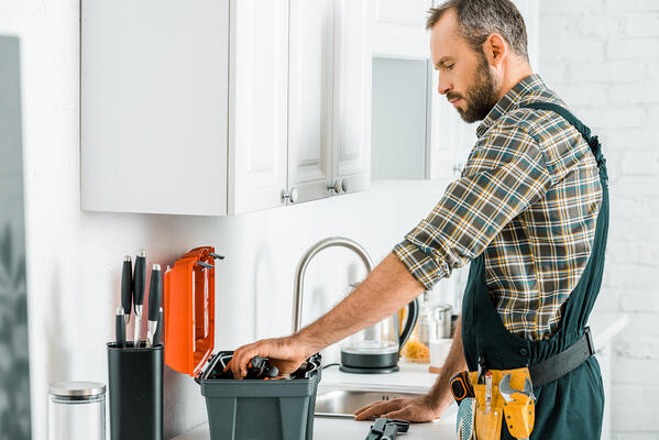 Side view of handsome plumber taking tools from toolbox in kitchen