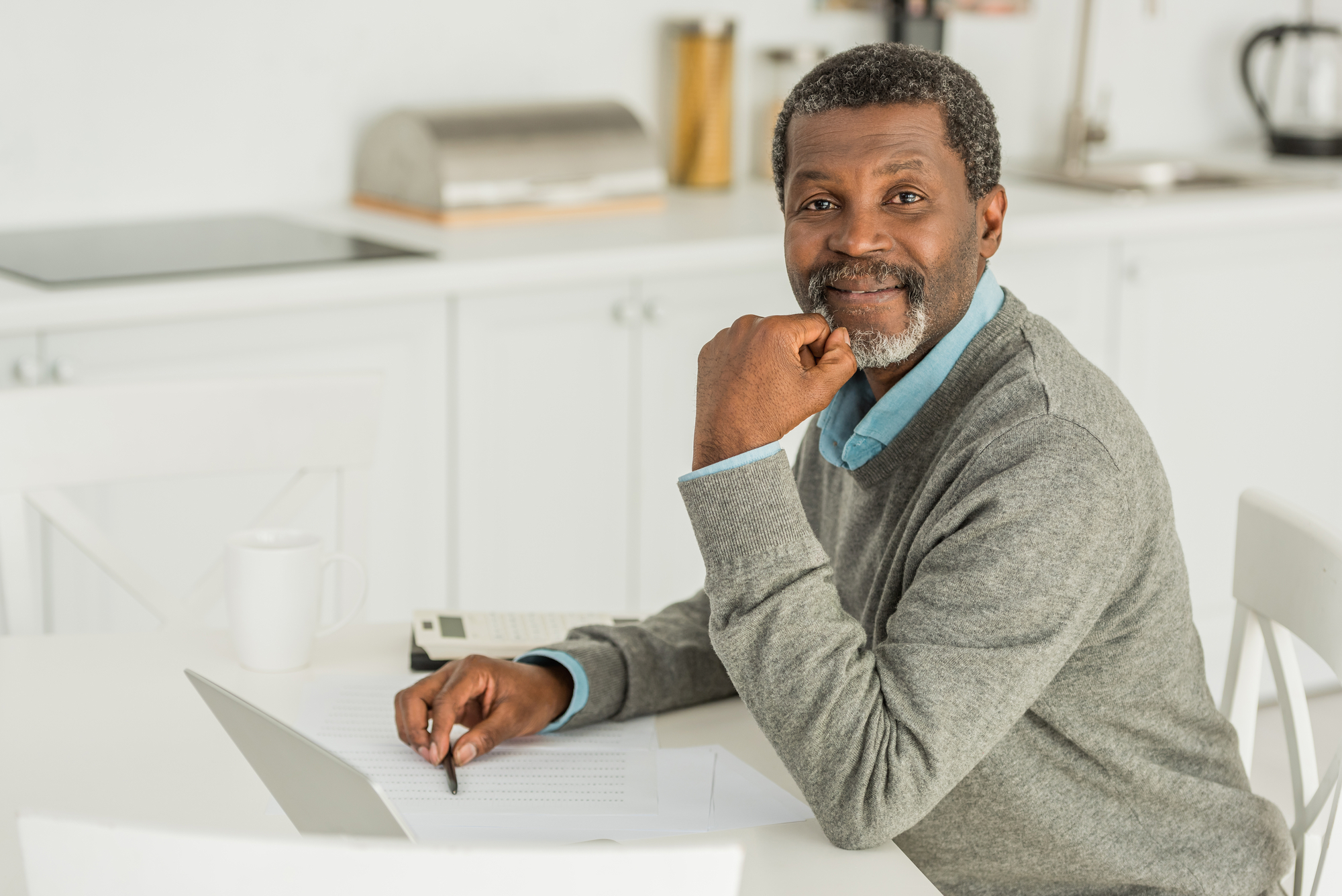 Smiling african american man looking at camera while sitting at table near laptop