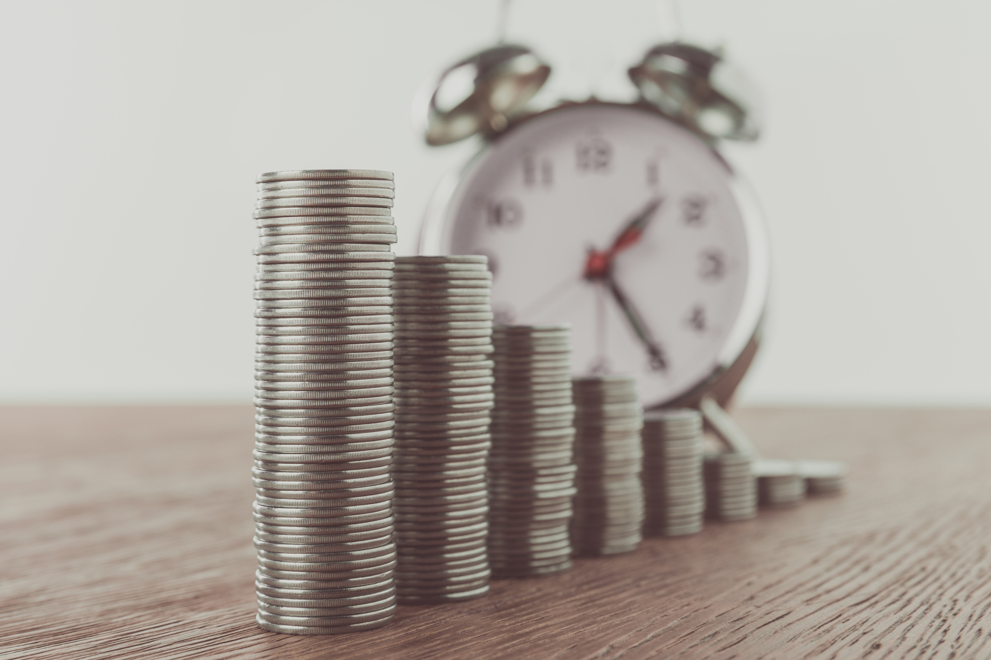 Stacks of coins and alarm clock on tabletop, saving concept