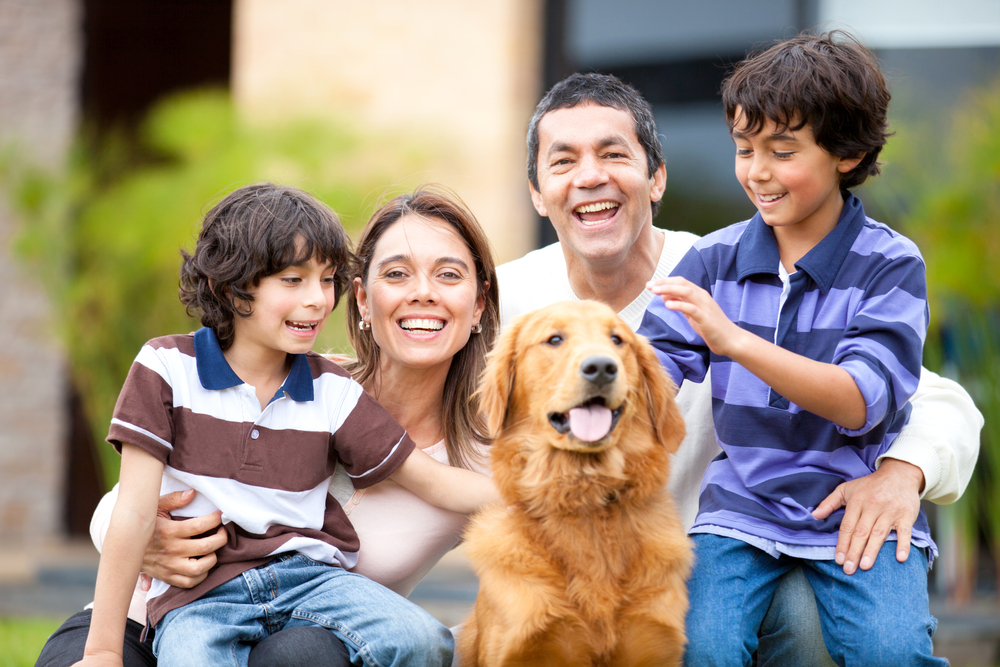 Family outdoors with a dog looking very happy
