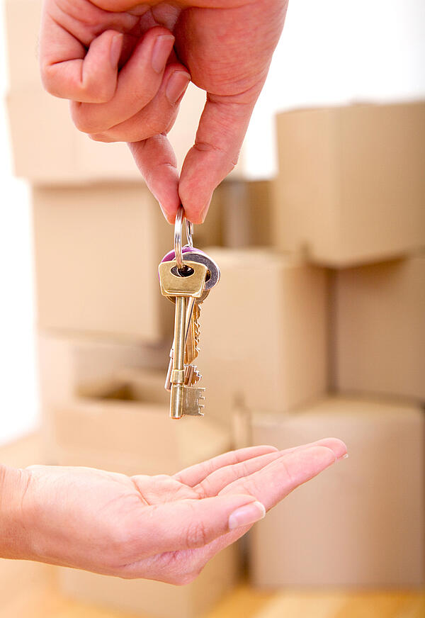 Person handing over the keys of a new house moving concepts