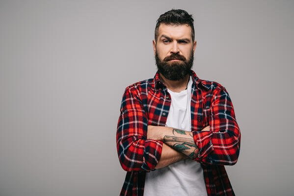 Suspicious bearded man in checkered shirt with crossed arms isolated on grey