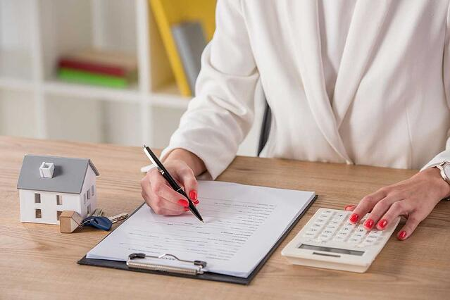 Partial-view-of-businesswoman-using-calculator-and-writing-in-contract-near-house-model-and-keys