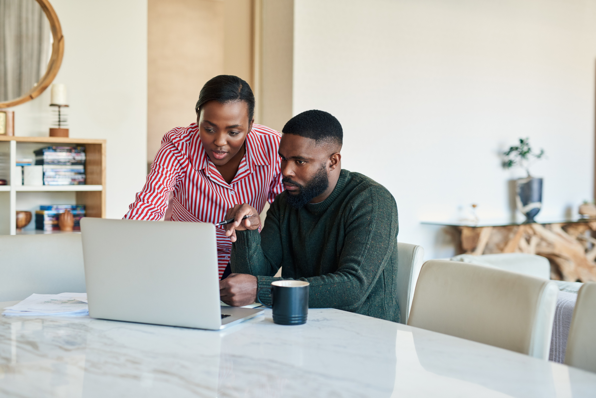 Young African American couple doing some online banking together at their dining room table at home