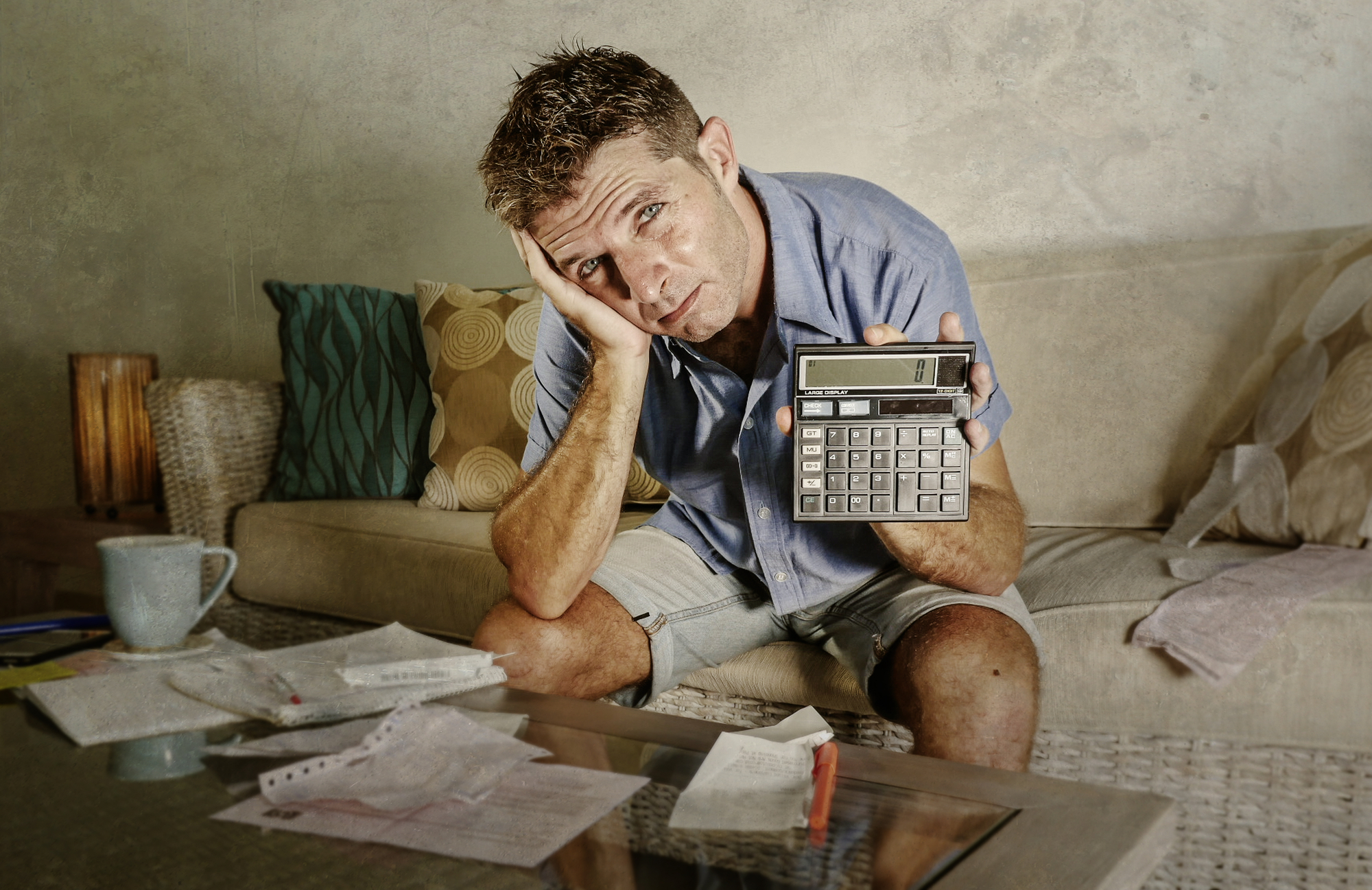Young attractive worried and stressed man at home calculating month tax expenses with calculator accounting payments doing bank paperwork in stress looking desperate suffering financial problem
