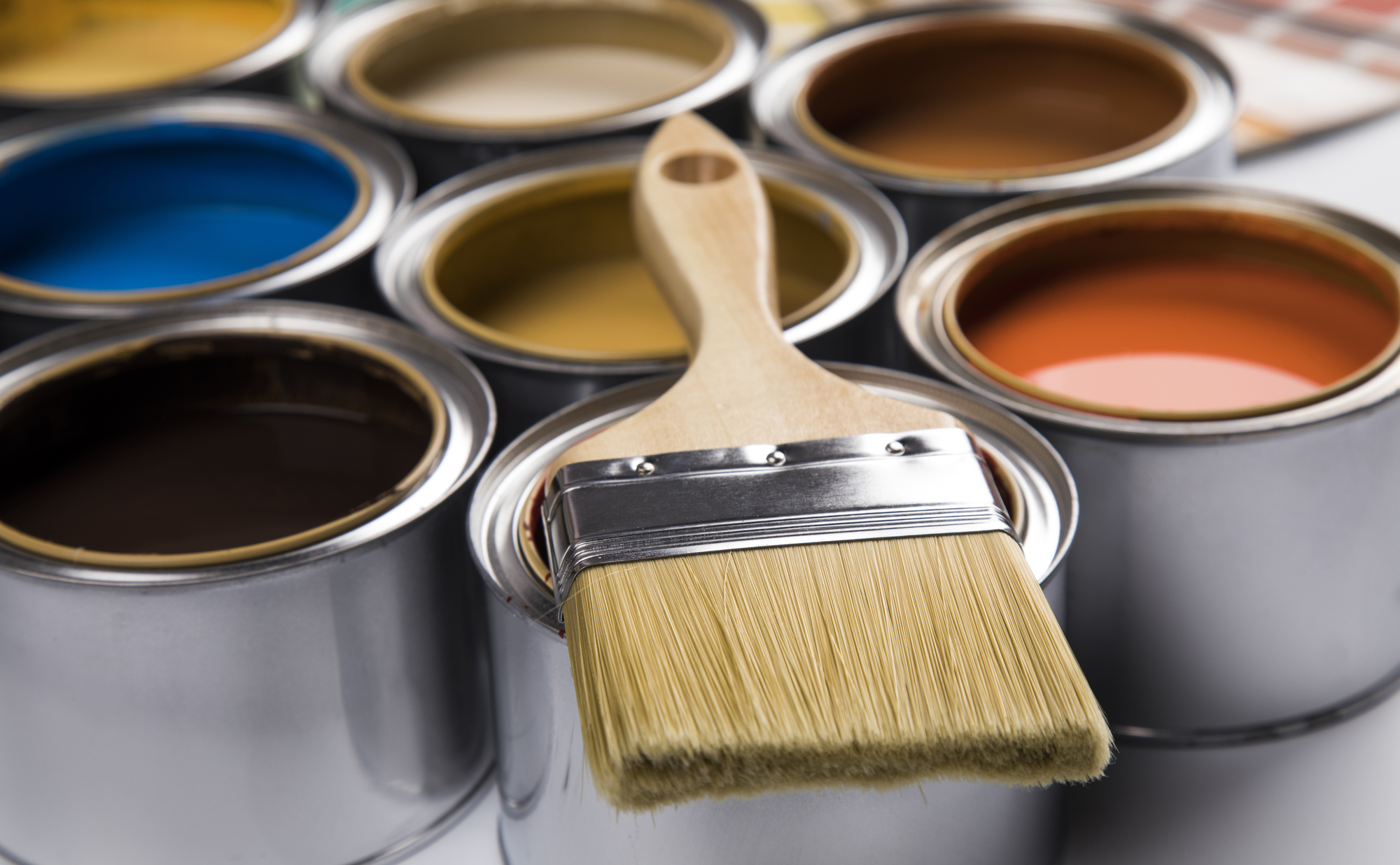 different colored paint cans and paint brush