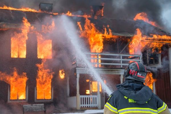 fireman hosing burning house