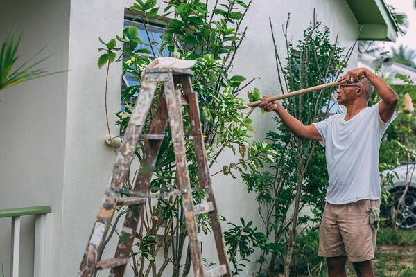 man painting wall outside a house